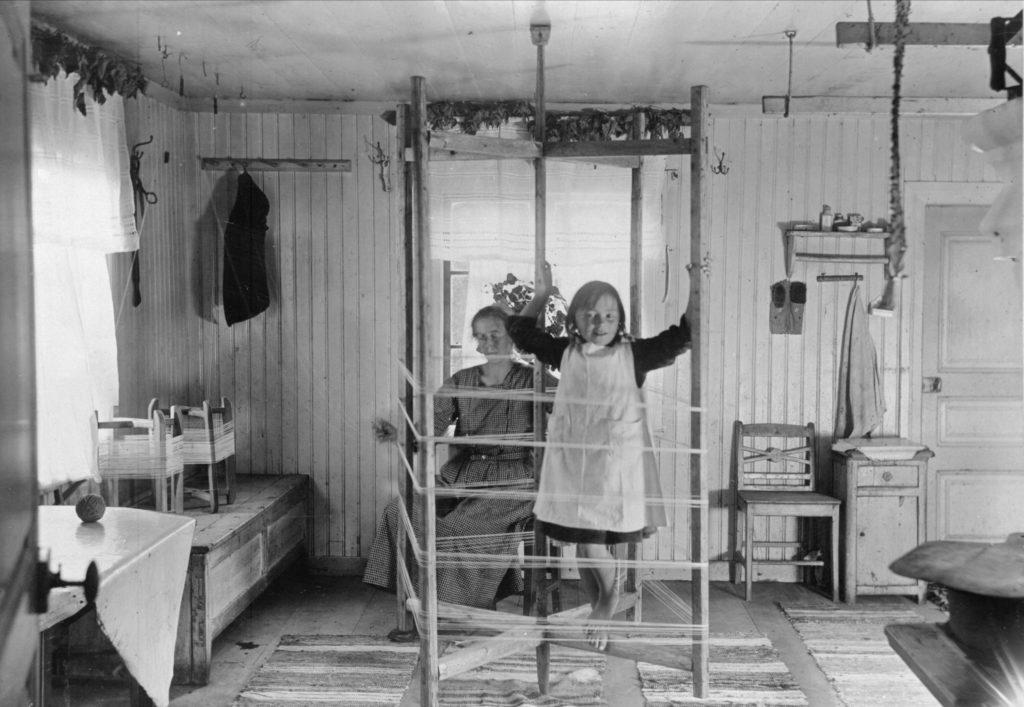 Gammal interiör i finngård. Flicka klättar på en varpställning.